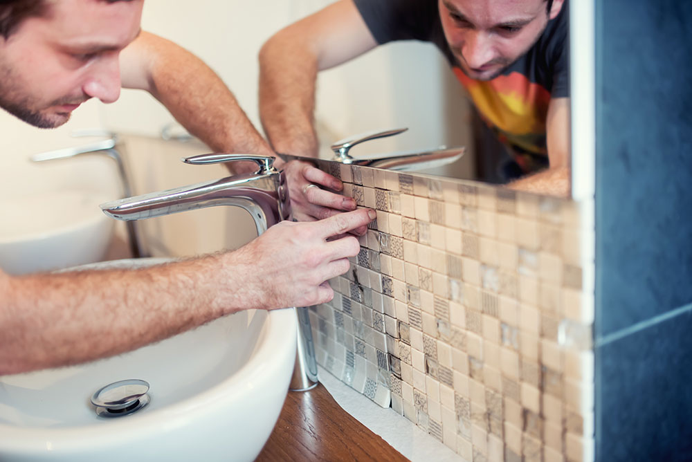 man fitting tiles in a newly renovated bathroom